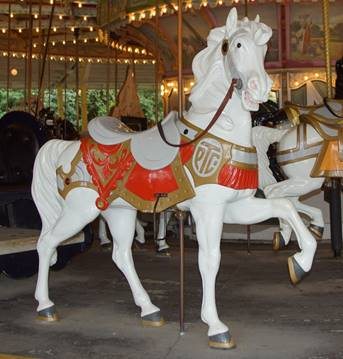 A horse statue in front of a carousel