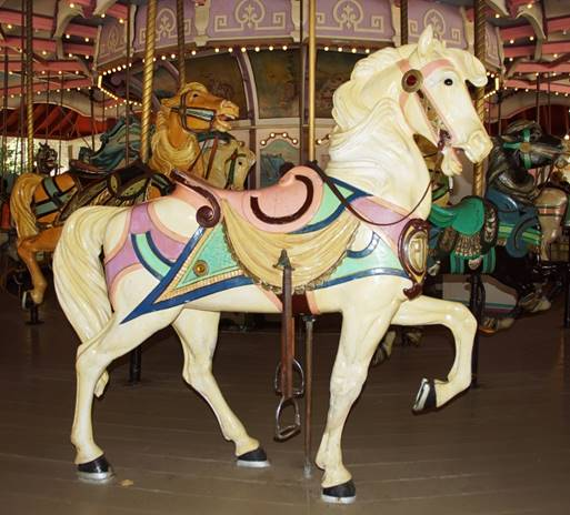 A group of people standing next to a carousel horse  Description automatically generated
