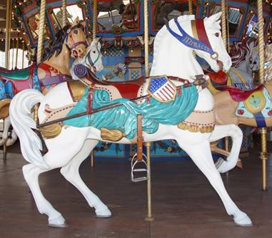 A person standing in front of a carousel horse