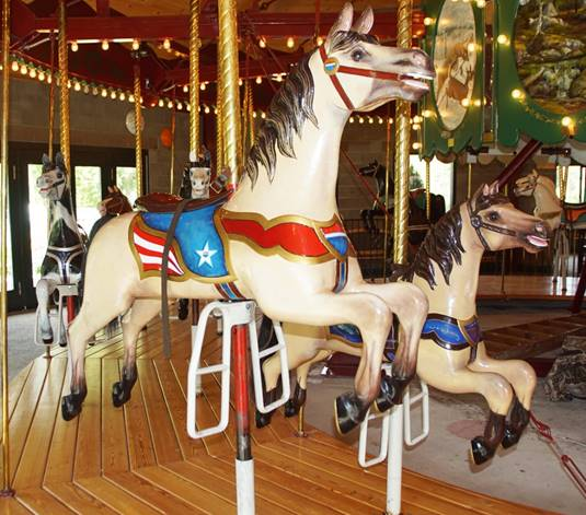 A picture containing carousel, ride, outdoor object, building  Description automatically generated
