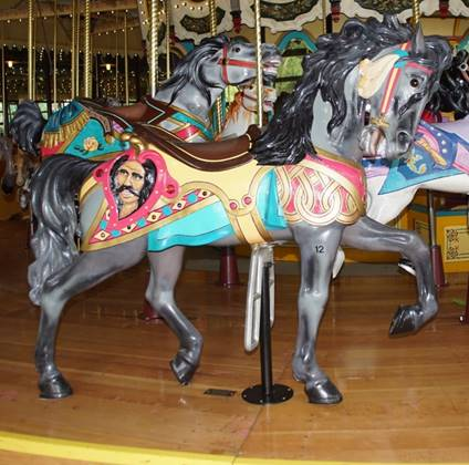 A group of people standing in front of a carousel horse  Description automatically generated