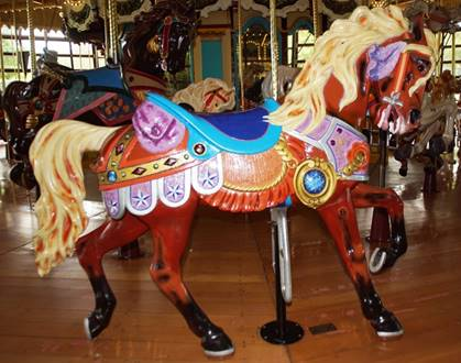 A person riding a horse in a carousel  Description automatically generated