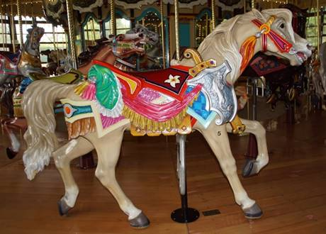 A person standing in front of a carousel  Description automatically generated